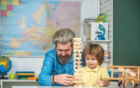 Father looking at son playing wooden block game. Little boy pupil with happy face expression near desk with school supplies. Young happy family father and son schooling math together