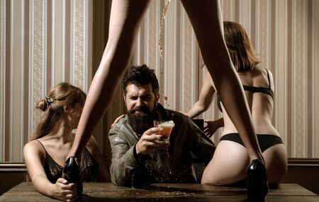 Sexy hot woman with beautiful long legs standing at table and drawing some beer for handsome bearded man at public house. Bearded man drinking beer and surrounded by sexy hot women.