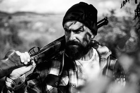 Poacher in the Forest. Bearded hunter man holding gun and walking in forest. Hunting Licenses. Hunter with shotgun gun on hunt. Stock Photo