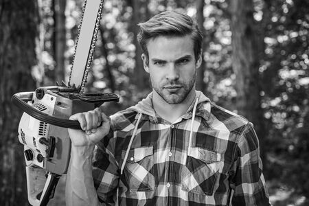 Lumberjack worker standing in the forest with chainsaw. Chainsaw. Stylish young man posing like lumberjack. Woodcutter with chainsaw on sawmill. Harvest of timber.