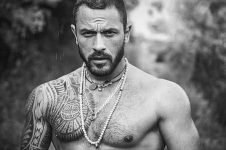 Brutal handsome man with tattooed body. Men tattoo casual fashion. Portrait of brutal handsome male model outdoor. Muscular athletic male with muscular torso