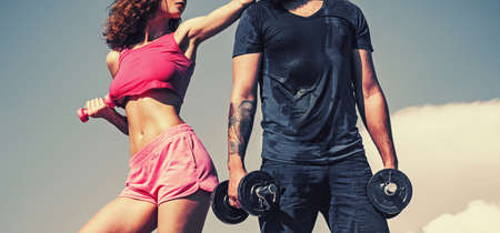Sporty couple on workout. Fitness and sports clothes. Activity couple doing sports on fresh air in the beach. Trainer training athlete for fitness. Athletics in summer sport shorts enjoying the sun. Фото со стока