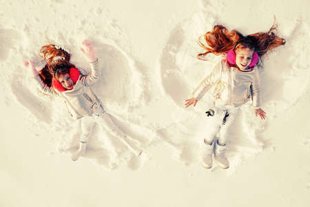 Snow angels made by a kids in the snow. Smiling children lying on snow with copy space. Funny kids making snow angel. Top view. 免版税图像