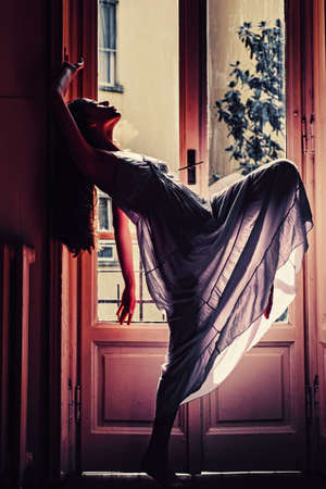 Woman meets morning near balcony. Relax time. Young woman standing near window.