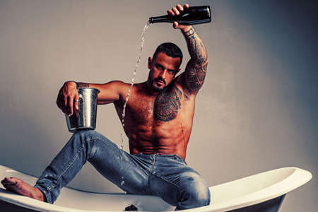 Wine festival concept. Champagne or wine celebration. Handsome brutal man pouring champagne in the bath on gray background.
