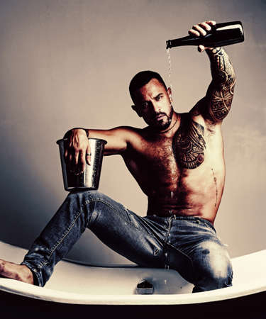 Champagne or wine celebration. Wine festival concept. Handsome man with tattooed body. Handsome brutal man on gray background. Mude male model with naked body. 免版税图像