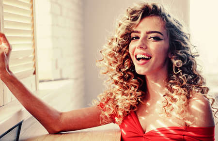 Beautiful woman. Shiny curly hair . Beautiful model woman with wavy hairstyle.