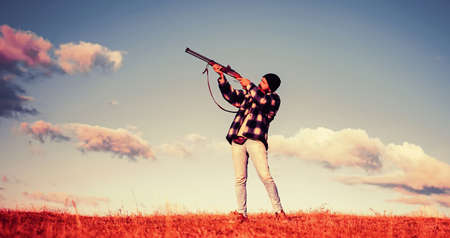 Sporting clay and skeet shooting. Hunter with shotgun gun on hunt. Autunm hunting. Hunting in USA. Hunter aiming rifle in forest. Process of duck hunting.