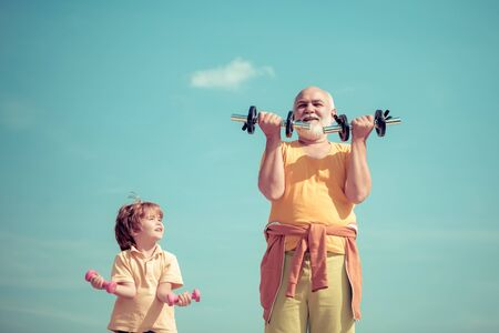 Follow grandfather. Grandfather and child is doing sport outdoors. Body care and healthcare. Father and child training together.