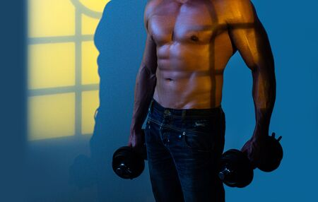 Muscular guy doing exercises with dumbbell over neon black blue background