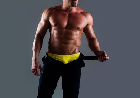 man with strong body. Torso man. Portrait of muscular shirtless man posing on blue neon background.