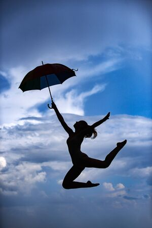 Woman jumping with umbrella. Ballet dancer isolated on sky background. Expressive artistic dance concept. Woman jump silhouette. Umbrella woman jump and sunset silhouette