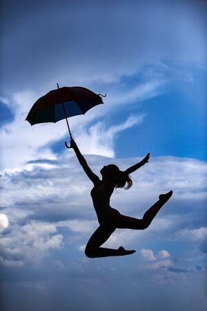 La donna che salta con l'ombrello. Ballerino di balletto isolato sul fondo del cielo. Concetto espressivo di danza artistica. Siluetta di salto della donna. Ombrello donna salto e tramonto silhouette