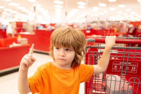 Toddler boy with shopping bag in supermarket. Child shopping in supermarket shop.