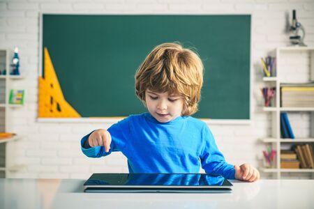 Pupil in class using digital tablet. Schoolboy with digital tablet in school classroom. Educational process.