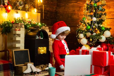Holiday discounts. Christmas. Little Santa Claus helper elf with a magic gift for Christmas. Check contents of christmas stocking. Family with kids celebrating Christmas at home. Banco de Imagens