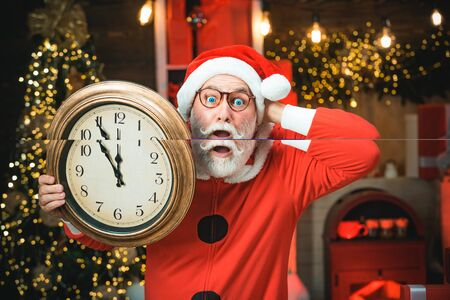 Santa Claus holding clock with countdown to Christmas or New Year Santa Claus in wooden home interior showing time on a clock. Santa Claus is looking at his watch.