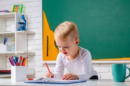 Kid gets ready for school. Cute little preschool kid boy with teacher study in a classroom. Elementary school and education. Фото со стока