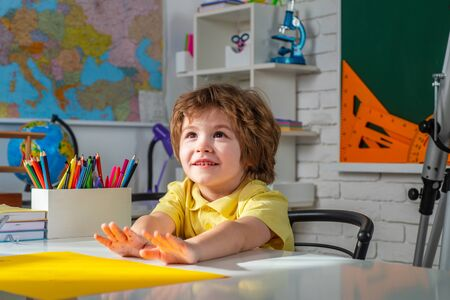 Child near chalkboard in school classroom. Educational process. Kids gets ready for school. Фото со стока - 147269159