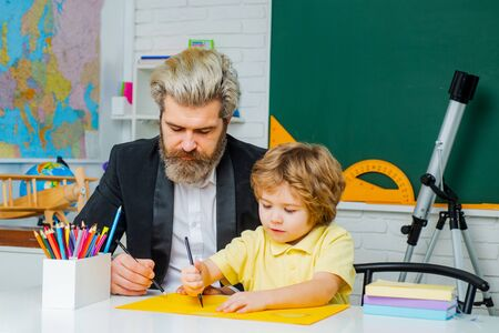 Father teaching son. Father and son together schooling. Kid and teacher is learning in class on background of blackboard.