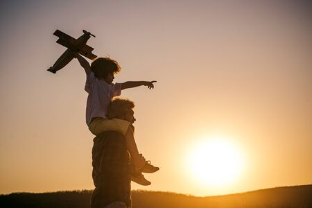 Father and son playing outside. Father and son playing in the park at the sunset time. Childhood memories
