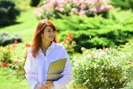 Red head female student with laptop computer. Spring Beautiful romantic red haired girl in lace dress standing in blooming garden. Banque d'images