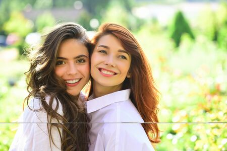 Friend Girls forever. Two cute lovely girl friends posing with smile on green spring background.