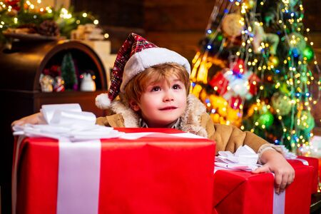 Child with big gift box. Merry Christmas and Happy Holidays. Kids enjoy the holiday. Christmas interior. Cute little child near Christmas tree. Banco de Imagens