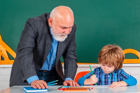 Senior teacher with pupil at back of classroom at the elementary school. Child at school lesson with senior teacher. Standard-Bild