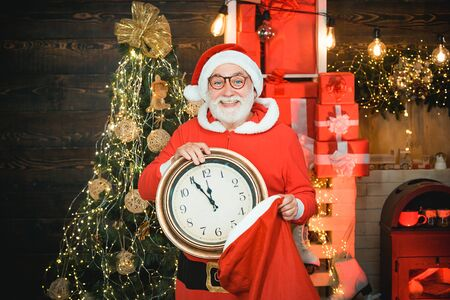 Santa make funny face and holding clock showing five minutes to midnight. Happy Christmas Santa. Its almost twelve clock.