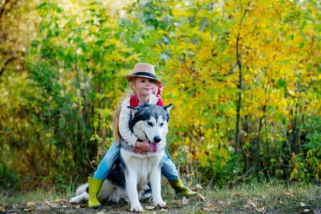Girl in hat hugging her dog. Little girl with her dog, alaskan malamute, full length. Child and dog on nature background. Carefree childhood. Nature walk with kids and pet. Kids with cute dog.