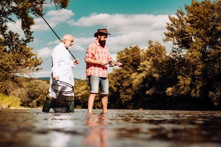 Elegant bearded man and brutal hipster fishing. Hobby sport activity. Master baiter. Father and adult son fishing lakeside. Friends men with fishing rod and net. Retired bearded fisher.