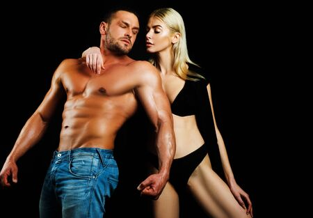 Muscular masculine man posing with his woman on black background. Black background.