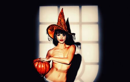 Night time halloween party for adult. Sexy stripper Woman with pumpkins. Halloween lingerie model. 版權商用圖片