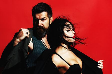 Portrait of sexy couple. Passion and sensual touch. Love concept. Valentines day. Portrait of sensual couple. Brunette girl in a black bra and bearded man on red background isolated. Фото со стока