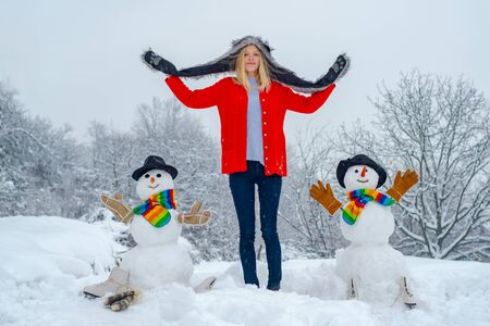 Happy winter girl making snowman. Christmas excited people outdoor . Woman Making snowman and having winter fun.