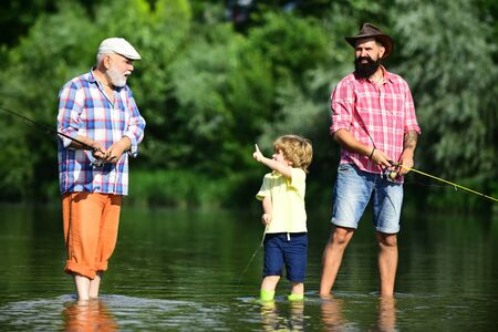 Little boy fly fishing in river with his father and grandfather.