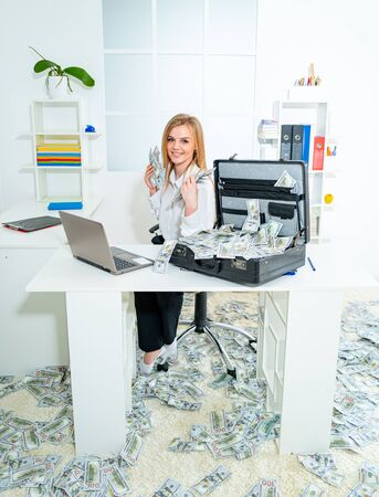 Young female worker businesswoman holding cash money and while working in office. Charming business woman sitting in office. Successful businesswoman holding money.