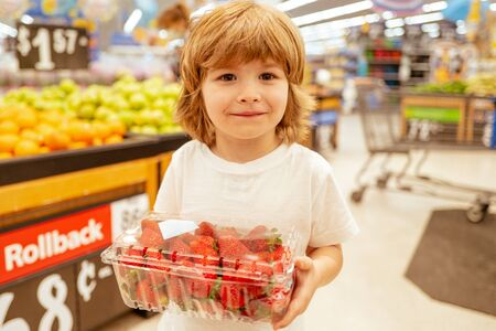 Happy little customer boy with strawberry, shopping at supermarket, grocery store. A boy is shopping in a supermarket. Supermarket, Shopping with Child.