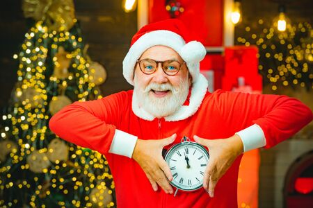 Thanksgiving day and Christmas. Santa Claus holding alarm clock against Christmas tree background. New year and Christmas time. Santa Claus at home. Banco de Imagens