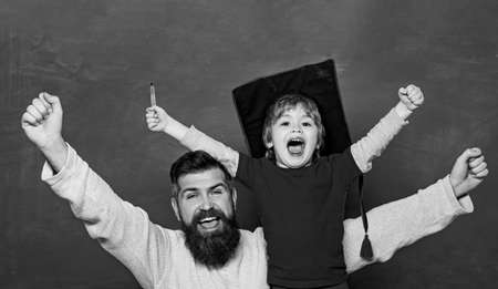Hooray. Daddy and son raising clenched fists in hooray gesture. Father teaching her son in classroom at school. Yeah good work. Happy father and son over chalkboard. Daddy and son together.