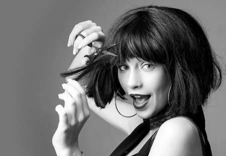 crazy girl with funny brunette hairdo. woman cut hair with scissors. hairdresser salon. Sensual woman. makeup and hair style. trendy look. Beauty and fashion. Woman with brittle hair. wig