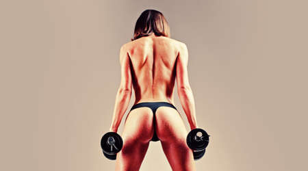Female fitness model. Middle eastern female doing biceps curl with dumbbells in the gym.
