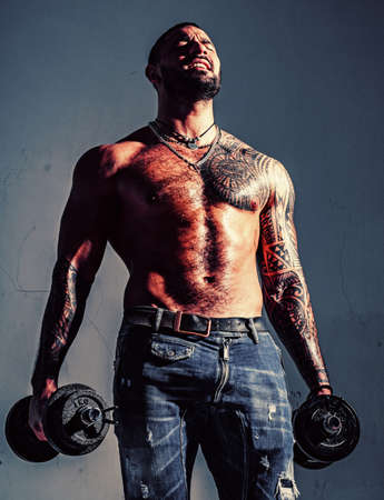 There is no limit to perfection. Macho confident face with muscular body sportsman bodybuilder. Muscular macho six packs hold dumbbells. Guy attractive working out. Muscular torso. Work out concept 版權商用圖片