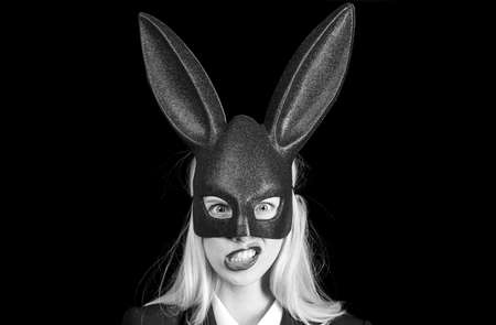 woman with mask Easter bunny on a black background and looks very sensually. Closeup of winking bunny girl face. woman wearing a mask Easter bunny and looks very sensually.