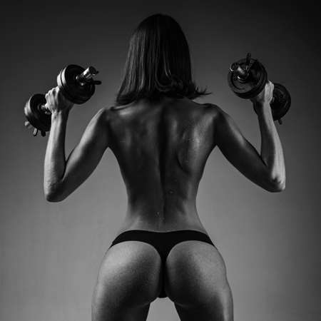 Attractive girl lifting dumbbell. Woman working hard in the gym. Healthy woman doing workout.
