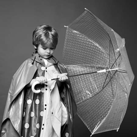 Autumn mood and the weather are warm and sunny and rain is possible. Cute little boy with colorfull umbrella. Rain and umbrella concept. Kids in rain. Foto de archivo