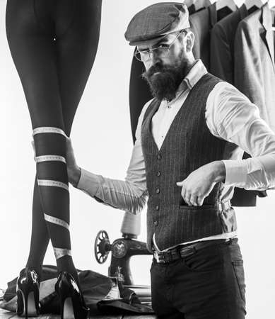 Bearded man dressmaking female clothes in designer store. Fashion designer or couturier at work