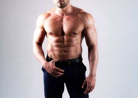 Strong man or muscular men. Bare torso. Young mans naked body on gray isolated background. Metrosexual concept.