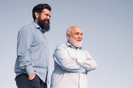 Handsome senior men in blue shirt. Portrait of two bearded men. Grandfather ageing. Male multi generation family walking. Fatherhood.